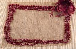 Kader van parels en bloemen op een achtergrond van jute wordt gemaakt die Royalty-vrije Stock Afbeelding
