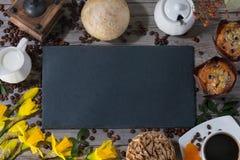 Kader van reeks van twee muffins, kop van aromakoffie, kruik room aan koffie en gele narcissen op grijze houten achtergrond met stock foto's