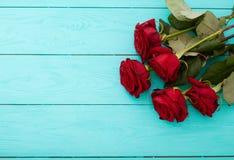 Kader van rode rozen op blauwe houten achtergrond Stock Afbeeldingen