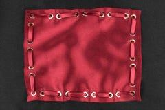 Kader van rode zijde met opgenomen rood satijnlint wordt gemaakt, op zwarte zijdeachtergrond die Stock Afbeeldingen