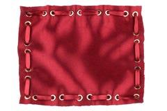 Kader van rode zijde met opgenomen satijnlint wordt gemaakt in gouden ringen die Royalty-vrije Stock Foto's