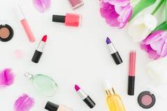 Kader van tulpenbloemen en schoonheidsmiddelen, lippenstift, nagellak op witte achtergrond wordt gemaakt die Hoogste mening Vlak  Stock Afbeelding