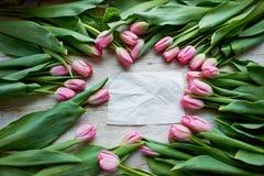 Kader van verse tulpen die op houten achtergrond met document worden geschikt Stock Afbeeldingen