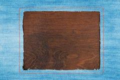 Kader voor de tekst van een jeansstof met de gestikte lijnen van een oranje draad, op een donkere houten oppervlakte Stock Fotografie