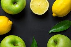 Kadersamenstelling van de verse ruwe groene organische bladeren van appelen sappige citroenen op zwarte achtergrond Gezonde leven royalty-vrije stock afbeelding