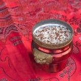 Kadzidłowy palnik z ryż na czerwonej tkaninie Fotografia Stock