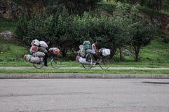 09/07/2018 Kaesong, Nordkorea: två hopplösa överlastade cyklar trampar in mot stad royaltyfri foto
