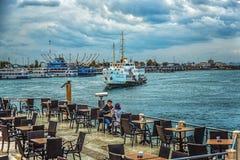 Kafé i Kadikoy port med sikt av sjösidan och den ankommande skytteln Royaltyfria Bilder