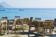 Kafé med trätabeller och stolar på sjösidan Royaltyfri Fotografi