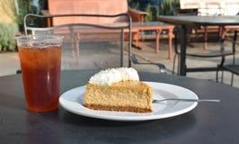 Kaféefterrättplats med pläterad pumpaostkaka, gaffel, med is te Royaltyfri Foto