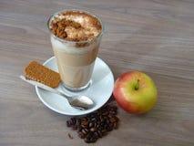 Kafélatte med det kanelbruna kexet och äpplet Fotografering för Bildbyråer