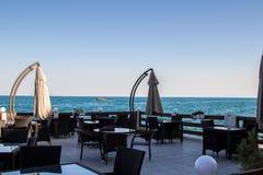 Kaféterrass, stängt paraply, blått havslandskap royaltyfri foto