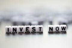 "Kafelkowi listowi koraliki literuje ""Invest now† tekst Fotografia Stock"