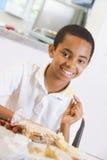 kafeteria som tycker om hans lunchskolaschoolboy royaltyfri fotografi