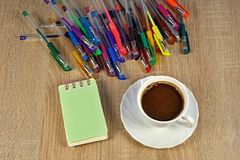 Kaffe anteckningsbok, mycket färgpennor Royaltyfri Bild