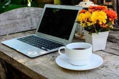 Kaffe bärbar dator på det wood golvet med blomman Royaltyfri Fotografi