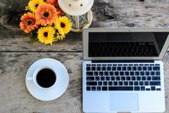 Kaffe bärbar dator på trätabellen med blomman Arkivfoto