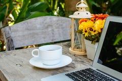 Kaffe bärbar dator på trätabellen med blomman Royaltyfri Foto