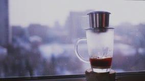 Kaffe dryper droppar i en kopp på en bakgrund av det stads- landskapet utanför fönstret Brygdkaffe i vietnames långsamt stock video