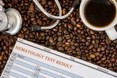 Kaffe- eller koffein- och för blodprov begreppsfoto Kopp med kaffe som omges av grillade bönor, resultat för hematological analys royaltyfria foton