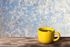 Kaffe eller te i gul kopp på trätabellen mitt emot beautif arkivfoto