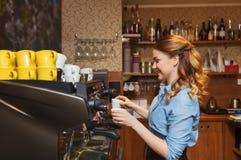 Kaffe för Barista kvinnadanande vid maskinen på kafét arkivbilder