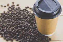 Kaffe för pappers- kopp som går, och kaffeböna arkivbilder