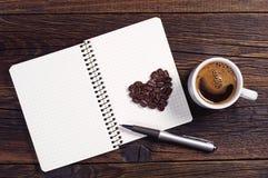Kaffe, hjärta och notepad Arkivbilder