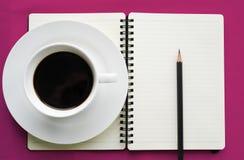 Kaffe i den vita koppen med den tidskriftsboken och blyertspennan Royaltyfri Foto