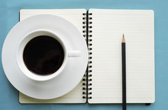Kaffe i den vita koppen med den tidskriftsboken och blyertspennan Royaltyfri Bild