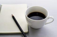 Kaffe i den vita koppen med den tidskriftsboken och blyertspennan Arkivbilder