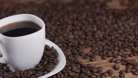 Kaffe i den vita koppen som omges av kaffebönor på mörk bakgrund i 4k UHD lager videofilmer