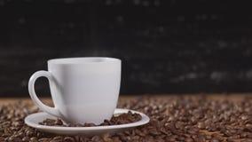 Kaffe i den vita koppen som omges av kaffebönor på mörk bakgrund i 4k UHD arkivfilmer