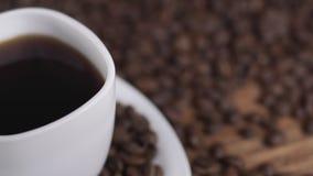 Kaffe i den vita koppen som omges av kaffebönor på mörk bakgrund i 4k UHD stock video