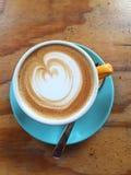 Kaffe i en gult kopp och blåtttefat Arkivfoton