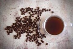 Kaffe i en härlig kopp på tabellen bland de spridda kaffebönorna arkivbilder