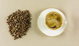 Kaffe i en kopp och i korn Arkivbild