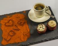 Kaffe i en kopp och två smakliga muffin och ordet älskar och hör Arkivbilder