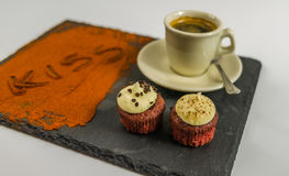 Kaffe i en kopp och två smakliga muffin och ordet kysser Arkivbild
