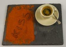Kaffe i en kopp på den svarta stenplattan och ordet kysser Royaltyfri Bild
