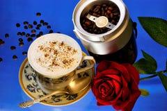 Kaffe i en naturlig stärka läcker drink för kopp och drottningen av blommor steg för ett festligt glat lynne, på en ljus blått arkivfoto