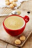 Kaffe i en röd kopp med ljusbruna kakor arkivfoton