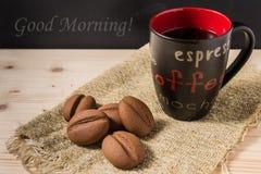Kaffe i en svart rånar med kakor på den lantliga tabellen Arkivfoton