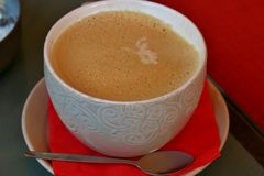 Kaffe i en vit kopp med en modell på ett tefat med en röd servett royaltyfri foto