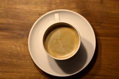Kaffe i en vit kopp med tefatet på trä-tabell fågelperspektiv arkivfoton