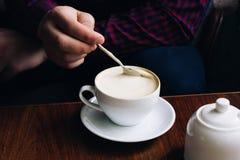 Kaffe i händer kvinna som kopplar av nära fönstret i en tappningrestaurang koffein är stärkande Cappuccino i ett exponeringsglas arkivfoto