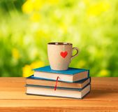 Kaffe i kopp med böcker på bokehbakgrund arkivbilder