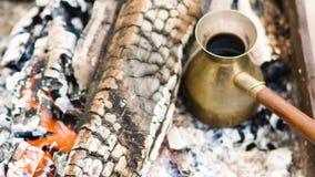 Kaffe i turk lagas mat i Cezve i varma kol, och handen för böldman` s tar bort kaffe från kol lager videofilmer