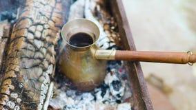 Kaffe i turk lagas mat i Cezve i varma kol, och handen för böldman` s tar bort kaffe från kol stock video