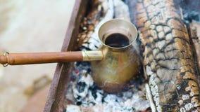 Kaffe i turk lagas mat i Cezve i varma kol, och handen för böldman` s tar bort kaffe från kol arkivfilmer